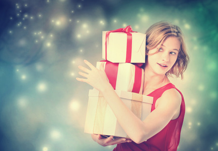 Happy young woman holding a many present boxes photo