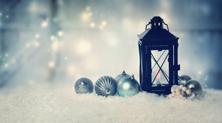 Christmas lantern with ornaments in the snow at night photo