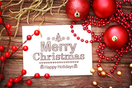 Red Christmas ornaments on wooden board with Merry Christmas message photo