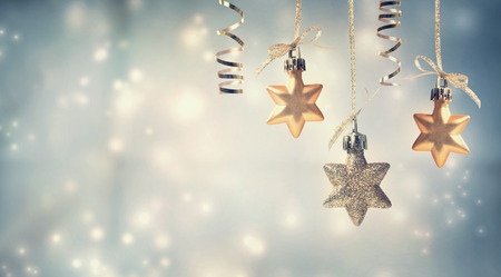 hanging on: Christmas golden star ornaments in snowy night Stock Photo