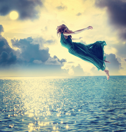 flying woman: Beautiful girl jumping into the blue night sky over the ocean Stock Photo