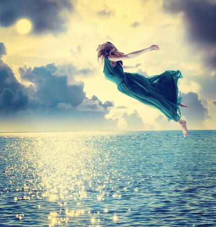 Muchacha hermosa que salta en el cielo azul de la noche sobre el océano