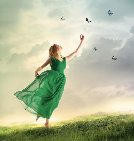山の上に蝶を追いかけて緑のドレスで美しい女性 写真素材