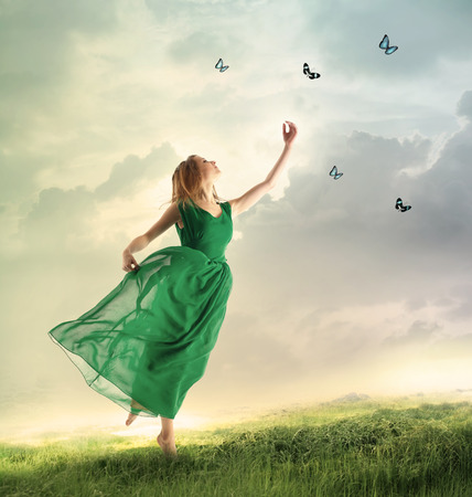 catching: Beautiful woman in a green dress chasing butterflies on a mountain