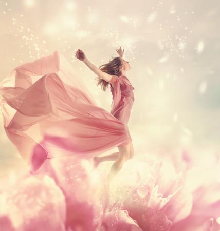 美しい若い女性は巨大な花にジャンプ