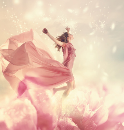 Beautiful young woman jumping on a giant flower Stockfoto