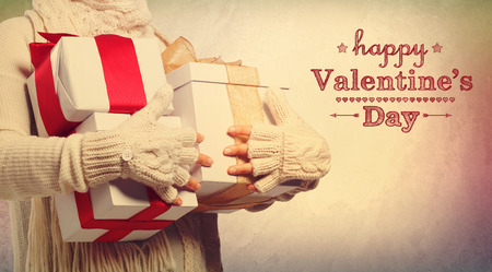 Happy Valentines Day message with woman holding present boxes photo