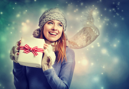 gift box: Happy young woman holding a present box in snowy night