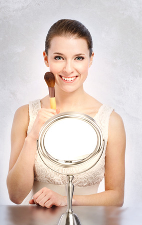 Beautiful young woman holding a makeup brush photo