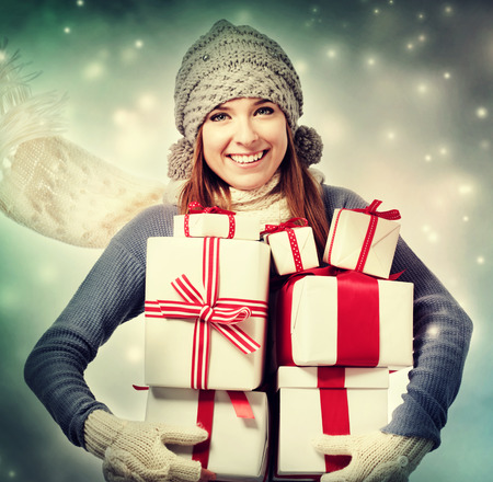Happy young woman holding many present boxes in snowy night photo