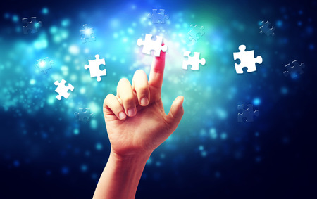 business support: Hand pressing a piece of puzzle over blue tech background Stock Photo