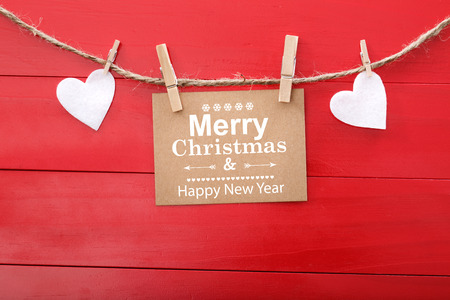 message: Merry Christmas and Happy New Year text and felt hearts with clothespins Stock Photo