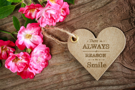 earthy: Inspirational heart shaped message card with flowers on wood Stock Photo