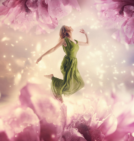 Beautiful young woman jumping on a giant flower 写真素材