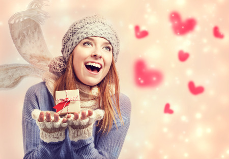 Happy young woman holding a small present box with red hearts photo