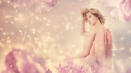 Beautiful woman in a striking pose in a pink peony flower fantasy
