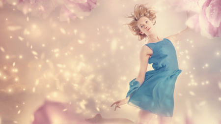 Beautiful woman in a blue dress in a pink peony flower fantasy photo