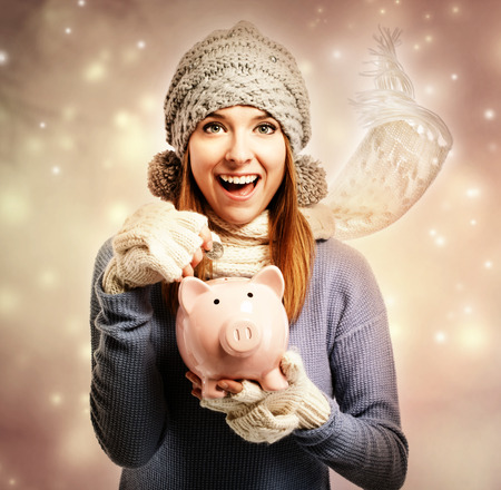 Happy young woman depositing money into her pink piggy bank photo