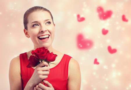 Gelukkige jonge vrouw in rode jurk met rode rozen