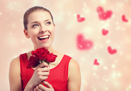 Happy young woman in red dress holding red roses