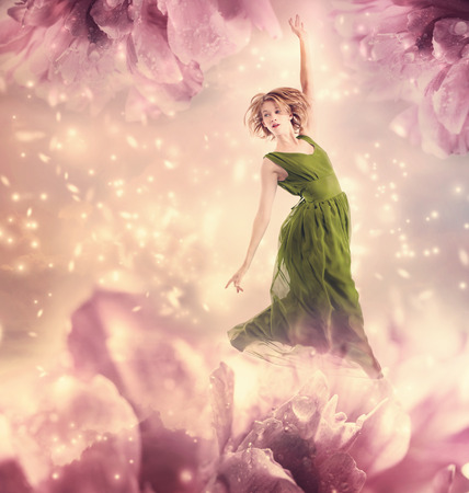 fairy tale princess: Beautiful woman in a green dress jumping in a pink peony flower fantasy