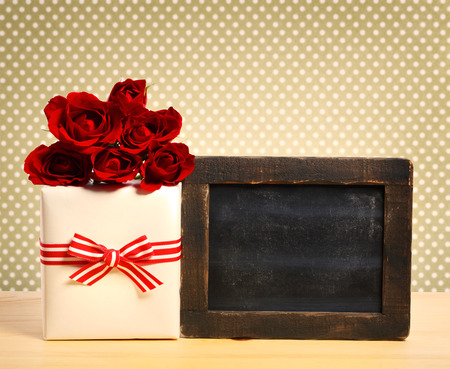 Present box with roses and blank chalkboard on polka dot background