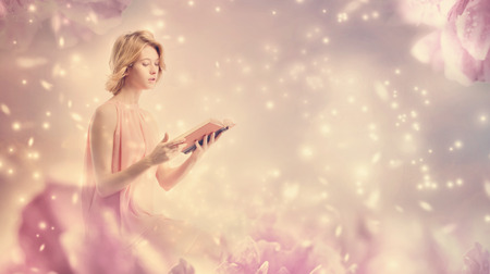 Young woman reading a book in pink peony fantasy environment Фото со стока