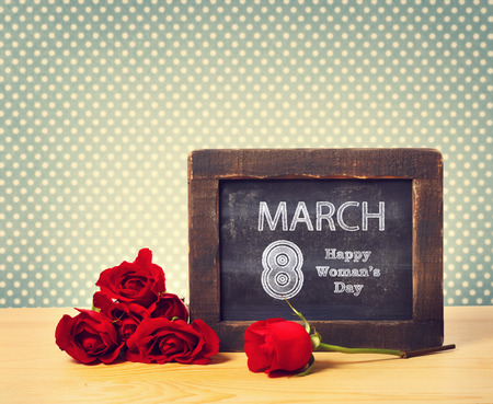 womans: Happy Womans Day March 8th written on little chalkboard with roses Stock Photo