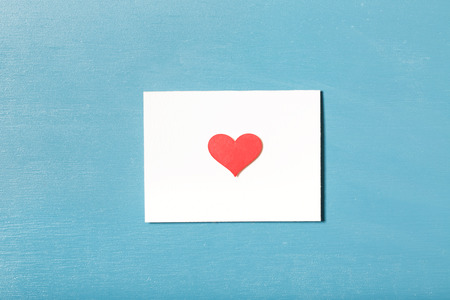 envelope: Card with hand crafted red heart on light blue wood background