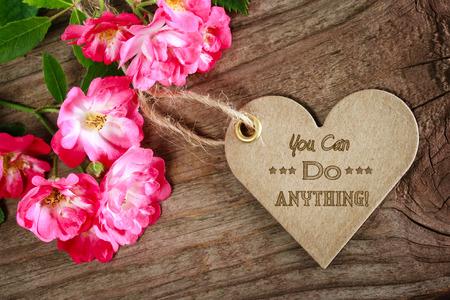 tu puedes: Usted puede hacer cualquier cosa! Tarjeta inspirada del coraz�n en forma de mensaje con las flores en la madera