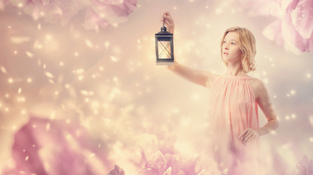 Young woman in a pink dress with a lamp in pink abstract flower background Stock Photo
