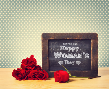 womans: Happy Womans Day message written on little chalkboard with roses Stock Photo