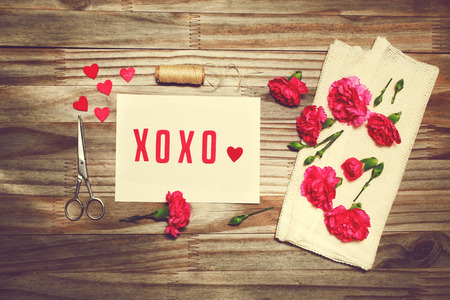 xoxo: Xoxo love theme with scissors, twine, and carnation flowers on grungy background