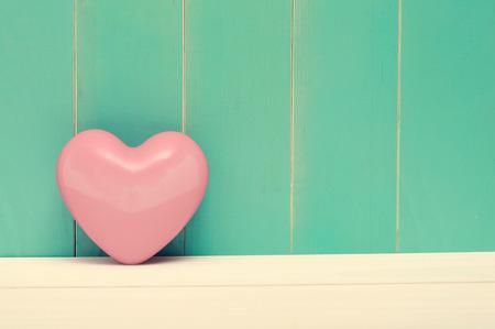 Pink shiny heart on vintage teal wood background