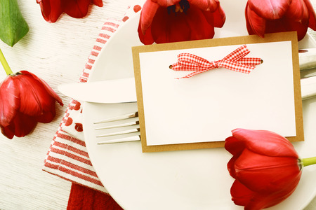 Romantic dinner table setting with blank note card and red tulips