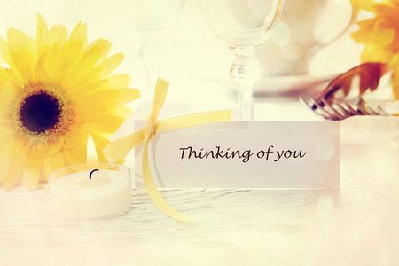 Thinking of you message card with table setting and yellow gerberas photo