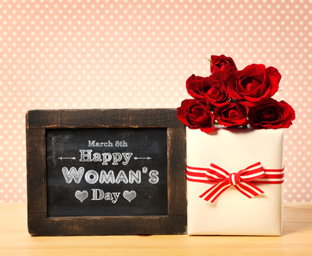 Happy Womans Day message written on little chalkboard with roses and present box