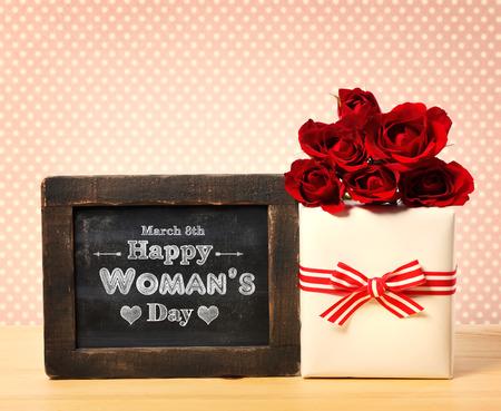 Gelukkig Womans Day bericht geschreven op kleine bord met rozen en huidige doos