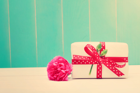 Small gift box with a pink carnation on teal colored wooden background