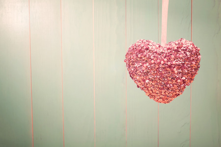 shiny day: Pink shiny heart hanging on vintage green wood background