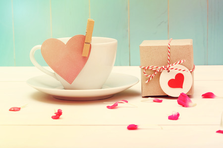spring message: Coffee cup with pink heart tag and a small giftbox