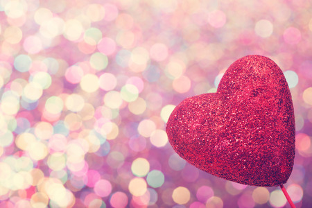 Red heart on abstract shiny colorful light background