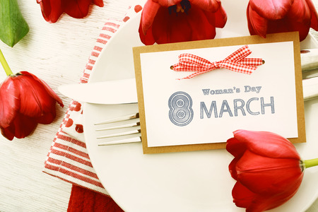 womans: Dinner table setting with Womans day message card and red tulips Stock Photo