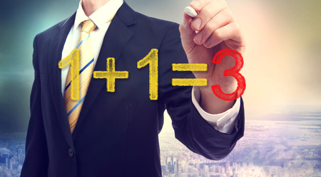 1: Businessman pointing at synergy concept 1+1=3 above the city Stock Photo