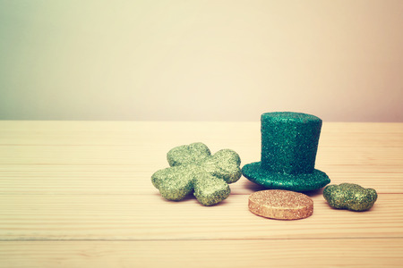 leprechaun background: Saint Patricks Day hat, coin, and clovers on rustic wooden board