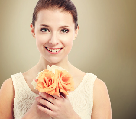 Beautiful young woman in a white dress holding roses photo