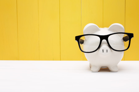Piggy bank wearing a black glasses over yellow wooden wall Imagens