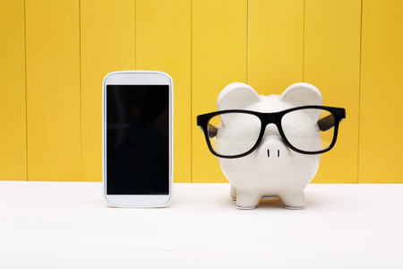 white piggy bank: Piggy bank wearing a glasses with a cellphone over yellow wooden wall