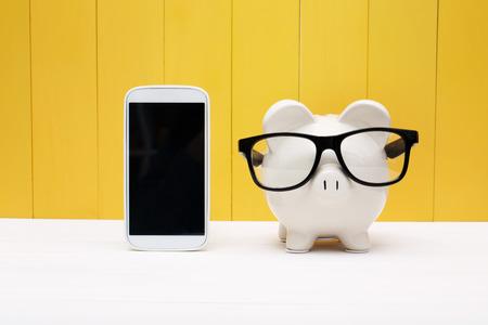Spaarvarken het dragen van een bril met een mobiele telefoon op gele houten muur Stockfoto