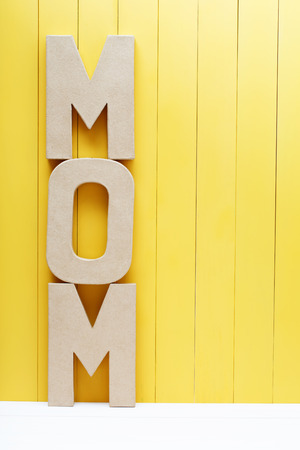 mothers day: MOM text in big cardboard letters on yellow wooden background Stock Photo